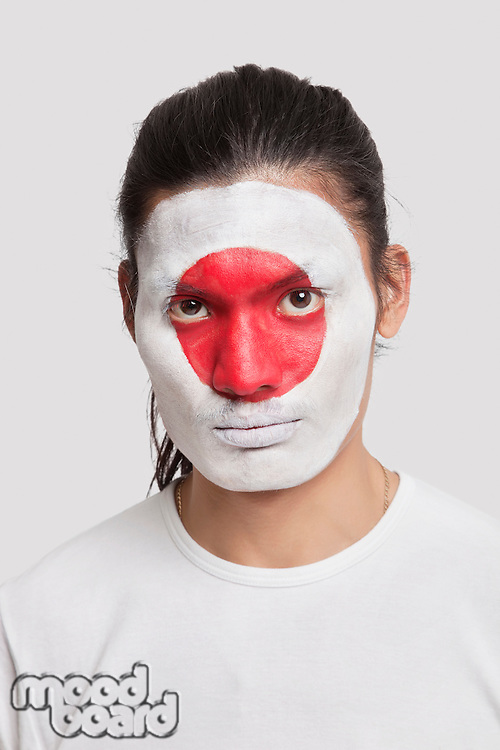 Portrait of serious young mixed race man with Japanese flag painted on face against white background