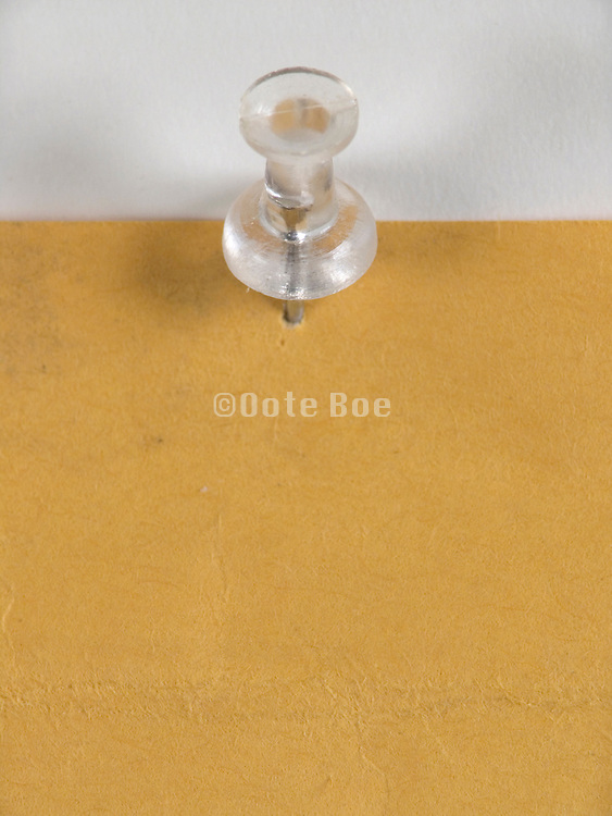 transparent push pin with paper pinned to wall