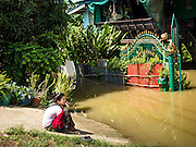30 SEPTEMBER 2016 - SAI NOI, AYUTTHAYA, THAILAND:  A woman waits for a boat to take her home in Sai Noi, a flooded village on the Chao Phraya River. The Chao Phraya River, the largest river that runs through central Thailand, has hit flood stage in several areas in Ayutthaya and Ang Thong provinces. Villages along the river are flooded and farms are losing their crops due to the flood. This is the same area that was devastated by floods in 2011, but the floods this year are not expected to be as severe. The floods are being fed by water released from upstream dams. The water is being released to make room for heavy rains expected in October.     PHOTO BY JACK KURTZ