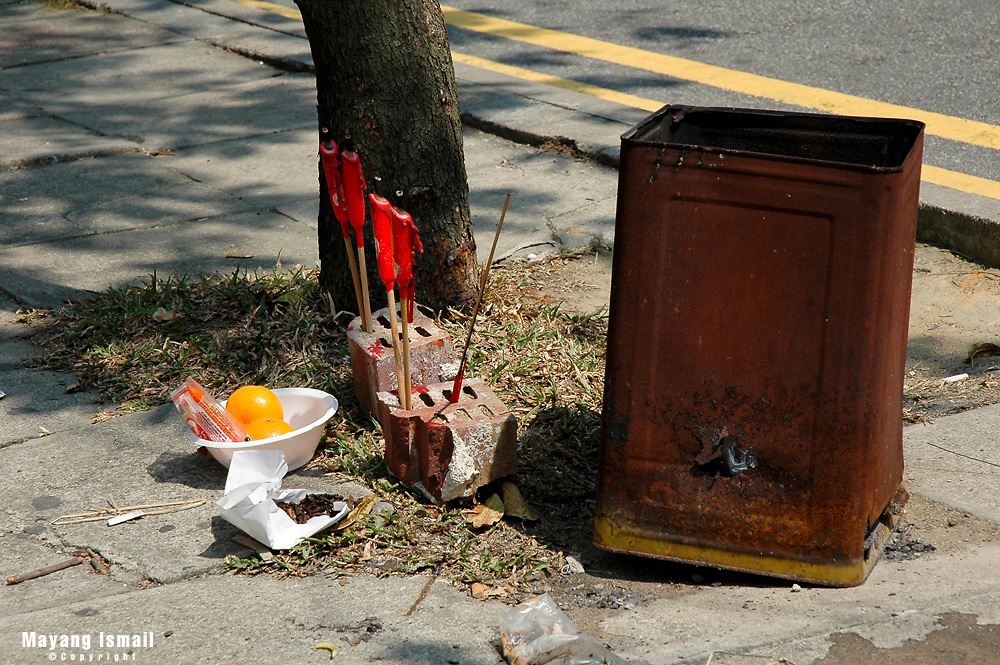 Joss sticks placed by the side of the road in Geylang, Singapore for a prayer session by the locals.