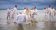As the tide rises again, players shake hands at the end of the annual Bramble Bank cricket match in the middle of the sea. The eccentric game involves members of the Royal Southern Yacht Club in Hamble playing against the Island Sailing Club from Cowes on the Brambles, a patch of sand in the Solent, only visible for a few minutes on the spring tide. The teams take turns in winning. This year the Royal Southern team won and hosted dinner at their club house.<br /> Picture date Monday 31st August, 2015.<br /> Picture by Christopher Ison. Contact +447544 044177 chris@christopherison.com