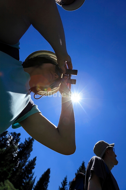 person looking through binoculars on a nature hiking trip
