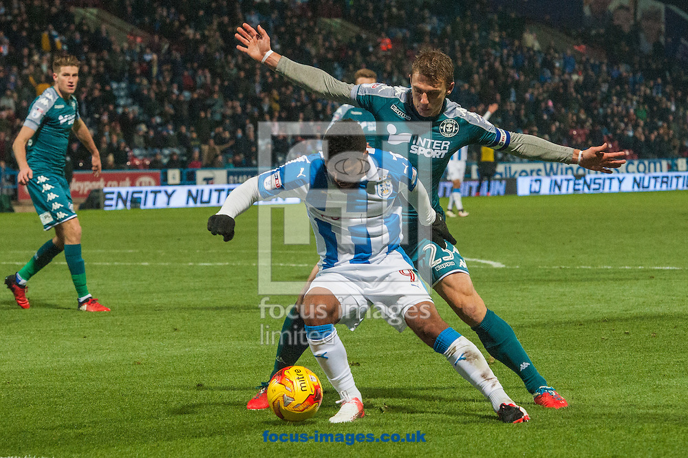 Elias Kachunga of Huddersfield Town is challenged by Stephen Warnock of Wigan Athletic during the Sky Bet Championship match at the John Smiths Stadium, Huddersfield<br /> Picture by Matt Wilkinson/Focus Images Ltd 07814 960751<br /> 28/11/2016