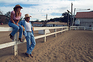Lifestyle portrait of rancher and his wife watch horses in corral in San Diego, CA.