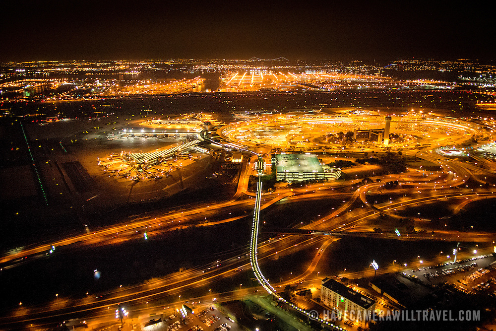 And aerial shot taken from a helicopter at about 500 feet of the terminals of Newark Liberty International Airport (EWR) at night, with the city lights showing brightly. The string of white lights from center to bottom of frame is the monorail (Airtrain). Please note that there is some high ISO noise at full resolution.