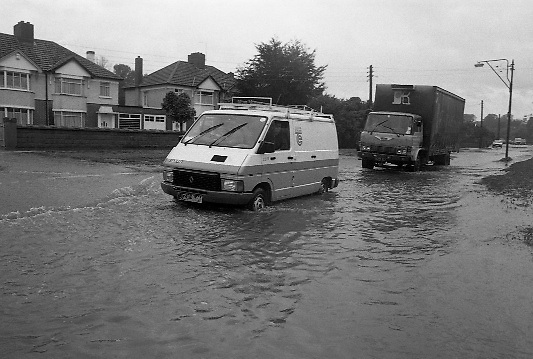 "Flooding at the Dodder..1986..26.08.1986..08.26.1986..28th August 1986..As a result of Hurricane Charly (Charlie) heavy overnight rainfall was the cause of severe flooding in the Donnybrook/Ballsbridge areas of Dublin. In a period of just 12 hours it was stated that 8 inches of rain had fallen. The Dodder,long regarded as a ""Flashy"" river, burst its banks and caused great hardship to families in the 300 or so homes which were flooded. Council workers and the Fire Brigades did their best to try and alleviate some of the problems by removing debris and pumping out some of the homes affected..Note: ""Flashy"" is a term given to a river which is prone to flooding as a result of heavy or sustained rainfall...Vans and trucks had an advantage going through the floodwaters,on the Lr. Dodder Road, Rathfarnham, as the sit higher off the ground"