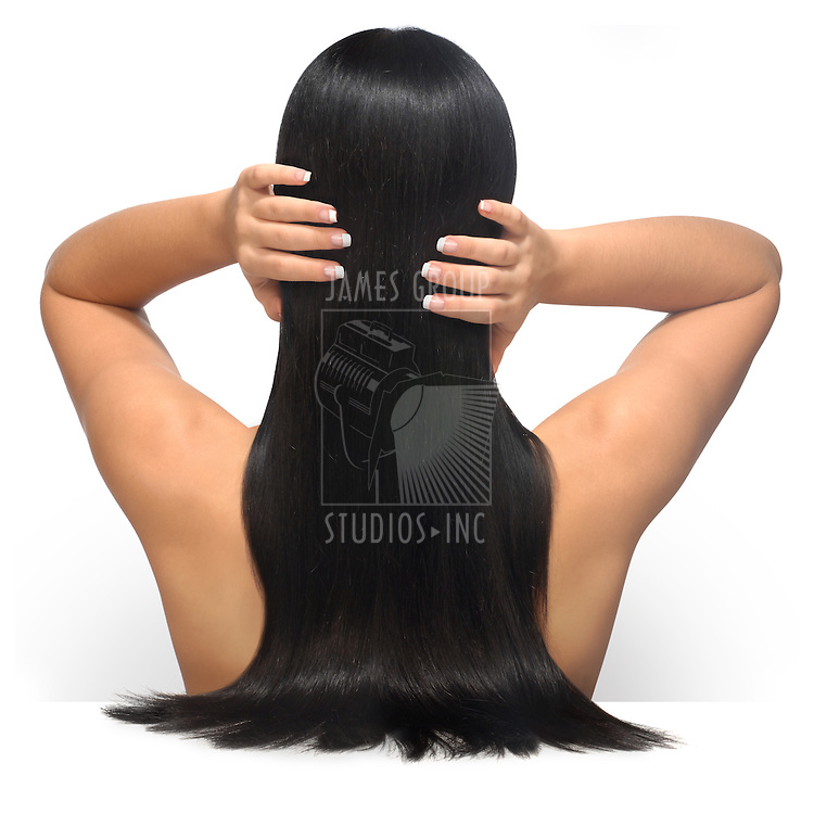 Young female model with long, dark, glamourous hair and a french manicure shot facing her back against a white background