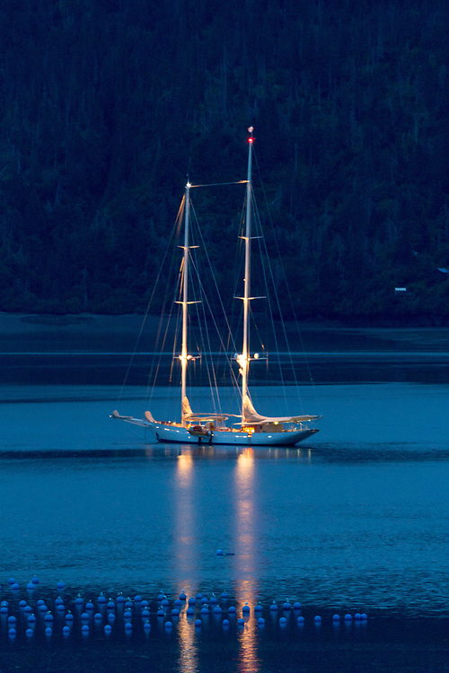 The superyacht Adela over a hundred years old and a hundred and eighty two feet. Sitting at anchor with oyster farms in the foreground. Halibut Cove, Alaska