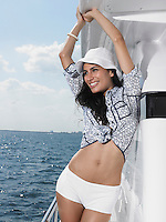 Young woman on yacht standing with arms raised and smiling