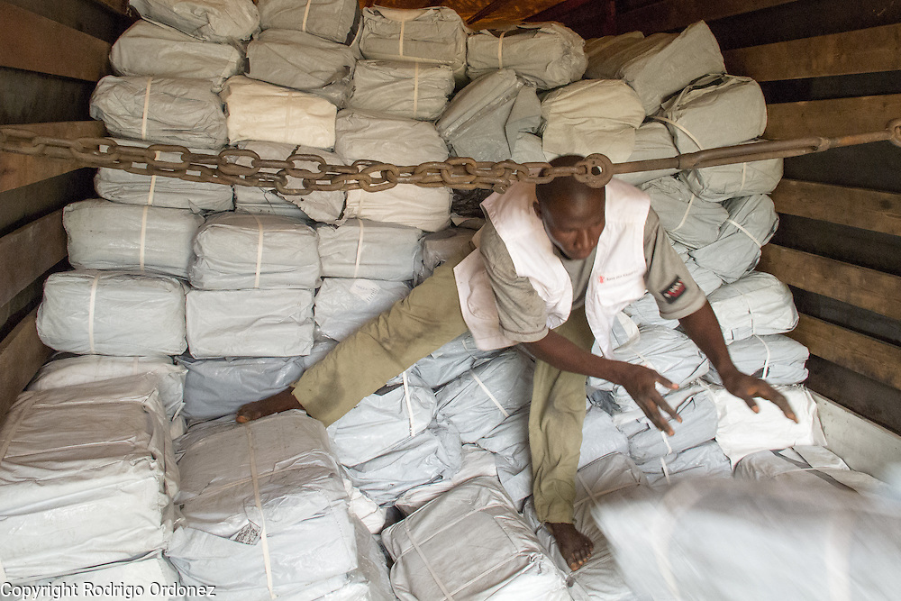 A temporary worker hired by Save the Children unloads a truck with relief items in Man, western C&ocirc;te d'Ivoire. <br /> Save the Children chartered a cargo plane carrying urgently needed items, including plastic sheeting, mosquito nets, buckets and water purification tablets. The children's charity will be handing out these basic supplies to 5,000 families displaced by conflict in western C&ocirc;te d'Ivoire to help prevent the spread of diseases.