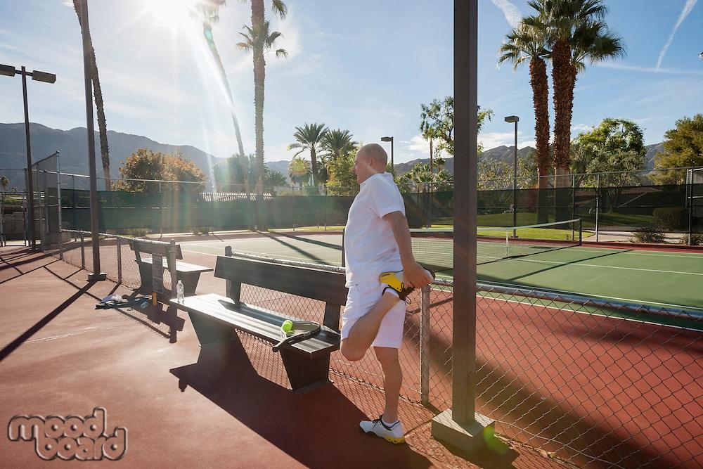Senior male tennis player stretching leg on court