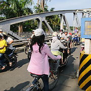Morning traffic of scooters crosses the Cau Phu Xuan bridge in Hue, Vietnam.