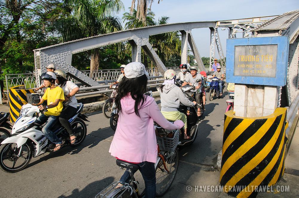 Morning traffic of scooters crosses the Cau Phu Xuan bridge in Hue, Vietnam.