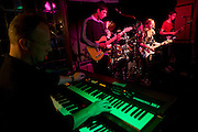 Adult keyboard player accompanies a teenage band perform  band in a south London pub.