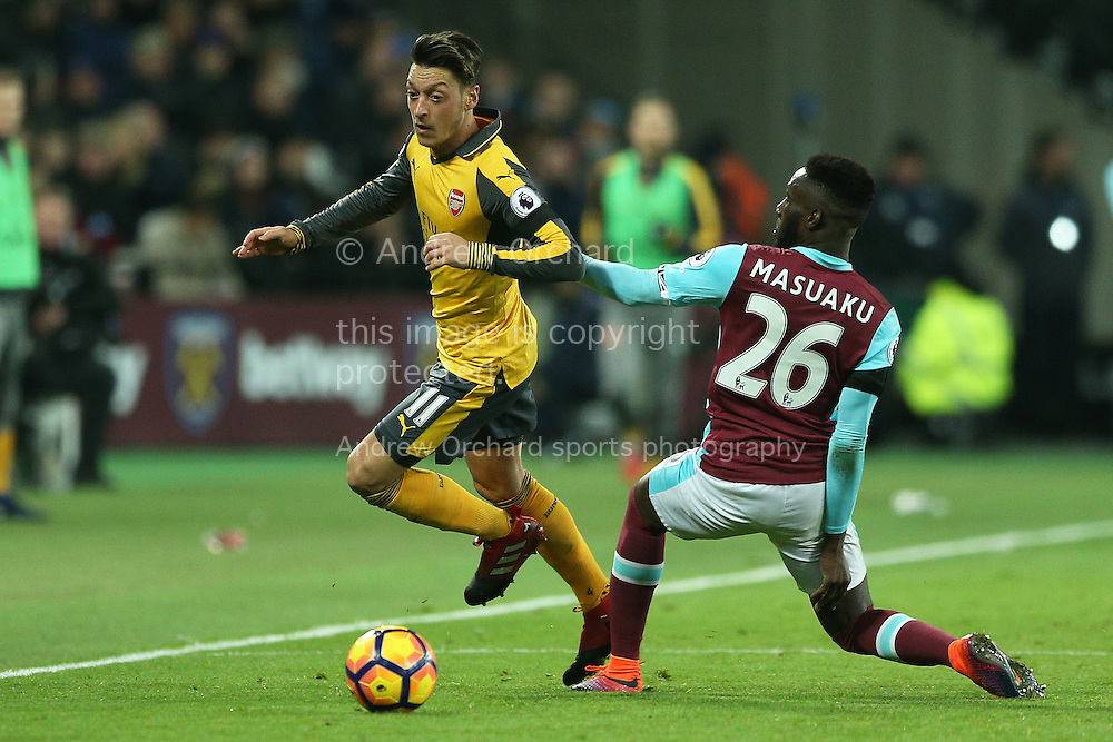 Mesut Ozil of Arsenal goes past Arthur Masuaku of West Ham United.Premier league match, West Ham Utd v Arsenal at the London Stadium, Queen Elizabeth Olympic Park in London on Saturday 3rd December 2016.<br /> pic by John Patrick Fletcher, Andrew Orchard sports photography.
