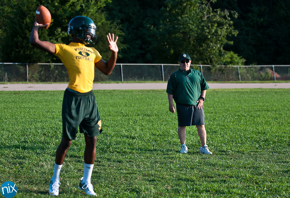 First year Central Cabarrus head coach Donnie Kiefer watches quarterback Hasaan Klugh warm up at football practice Monday July 30 at Central Cabarrus High School. (photo by James Nix)