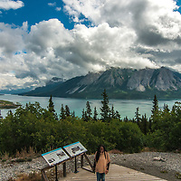Tutshi Lake. Bove island in left foreground. Tourist in foreground.