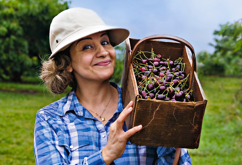 A healthy active woman in her mid-thirties beams at the camera and is holding a box of just harvested cherries on her shoulder. She is standing outdoors in an orchard wearing a white cap with brim and a blue and white plaid shirt.