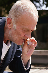 Man sitting on a bench smoking; Community Care Project user,