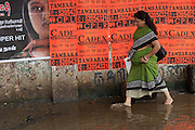 Woman walking through flooded street in Chennai.