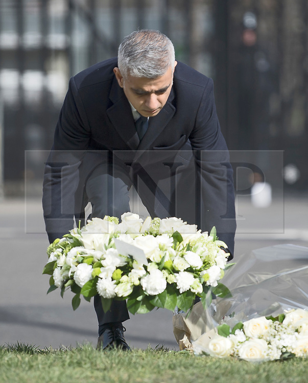 © Licensed to London News Pictures. 22/03/2018. London, UK. Mayor of London SADIQ KHAN places flowers at Parliament Square, outside the Houses of Parliament in Westminster, London on the one year anniversary of the the Westminster Bridge Terror attack. A lone terrorist killed 5 people and injured several more, in an attack using a car and a knife. The attacker, 52-year-old Briton Khalid Masood, managed to gain entry to the grounds of the Houses of Parliament and killed police officer Keith Palmer. Photo credit: Ben Cawthra/LNP
