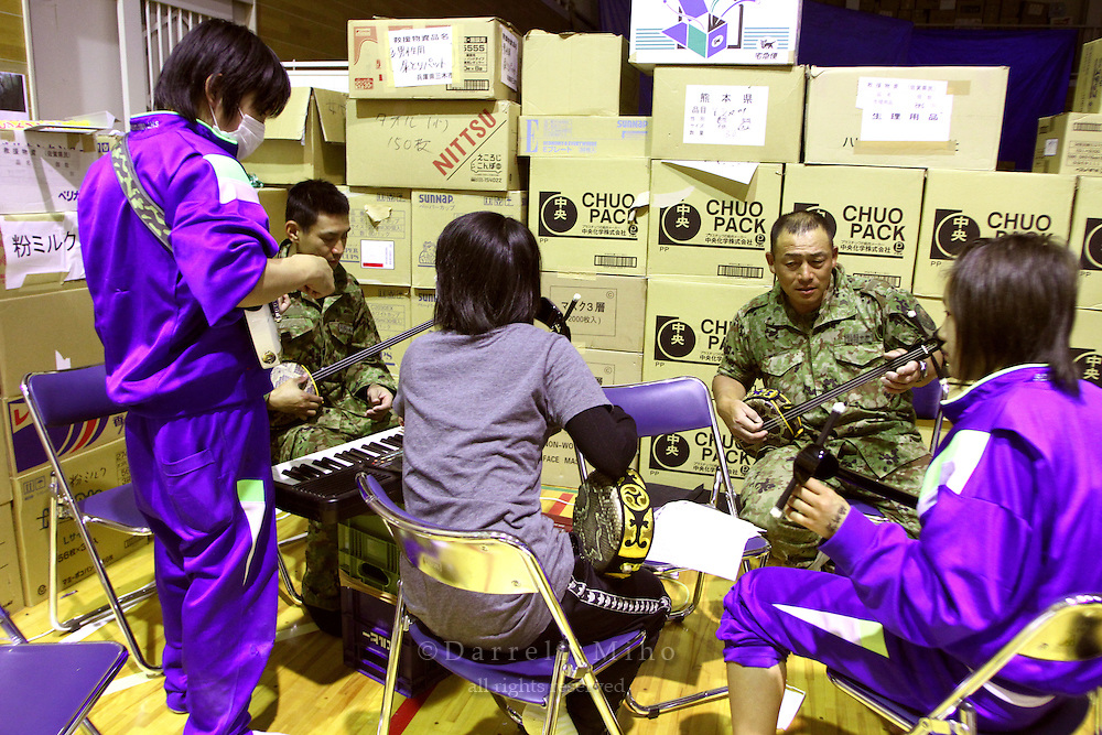 May 18, 2011; Minamisanriku, Miyagi Pref., Japan - Soldiers from Japan's Self-Defense Forces teach residents Sanshin, the Okinawan style of playing the shamisen, at the Shizukawa High School Evacuation Center in Minamisanriku after the magnitude 9.0 Great East Japan Earthquake and Tsunami that devastated the Tohoku region of Japan on March 11, 2011.