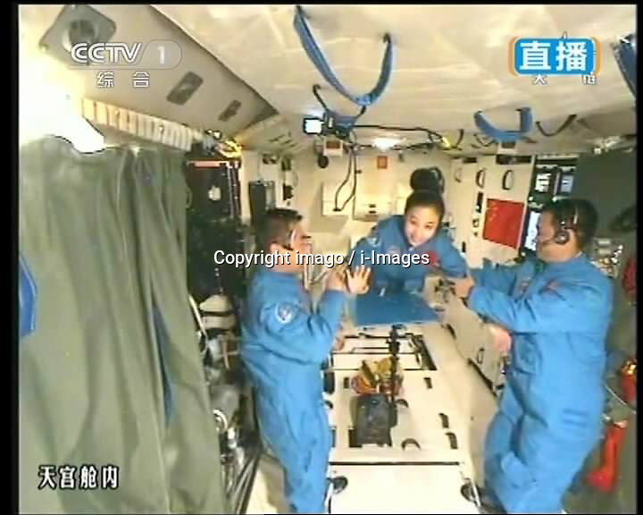 59870551  This TV grab taken on June 20, 2013 shows female astronaut Wang Yaping (C), one of the three crew members of Shenzhou-10 spacecraft, greeting students on Earth aboard China s space module Tiangong-1. A special lecture began Thursday morning, given by Wang Yaping aboard China s space module Tiangong-1 to students on Earth, Thursday June 20, 2013.<br /> UK ONLY