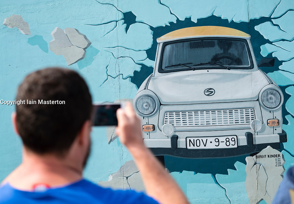 Tourist taking photograph of Trabant  mural painted on original section of Berlin Wall at East Side gallery in Berlin, Germany ...Editorial Use Only