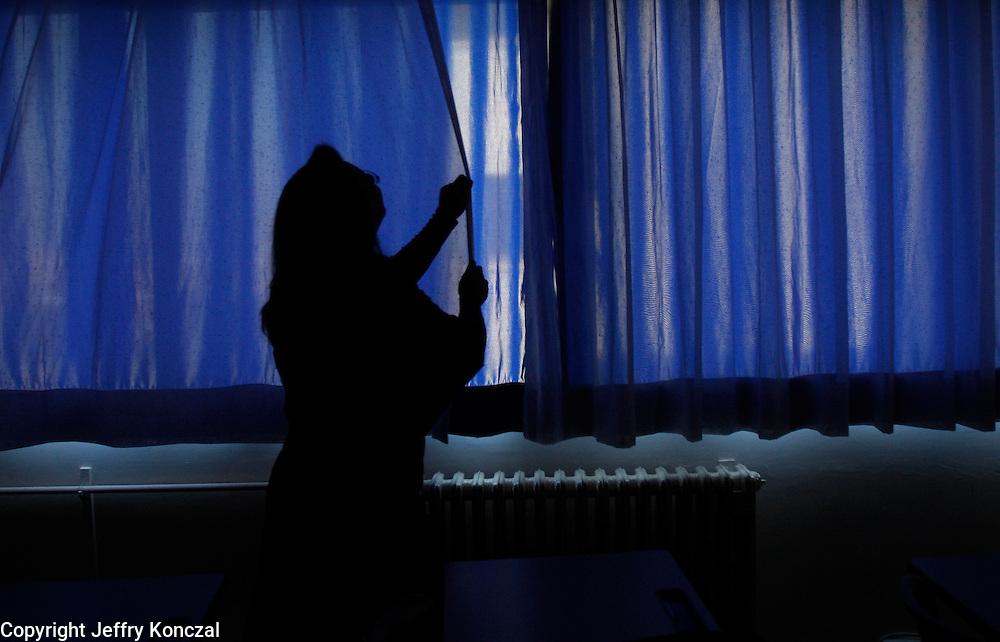 A teacher at a school shuts the blinds in a classroom in Ankara, Turkey.