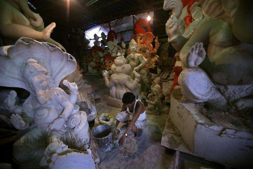 "Skilled labourer mixes plaster of paris inbetween unfinished Ganesha Idols in a workshop in Mumbai, September 6, 2007. Lord Ganesha idols are prepared for the ""Ganesh Chaturthi"" (the Ganesh festival), a popular religious festival in India.Photographer: Prashanth Vishwanathan"