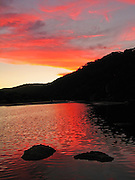 """Red and yellow sunset light strikes clouds over Tidal River at Wilson's Promontory National Park in the Gippsland region of Victoria, Australia. Drive two hours from Melbourne to reach Wilson's Promontory, or """"the Prom,"""" which offers natural estuaries, cool fern gullies, magnificent and secluded beaches, striking rock formations, and abundant wildlife."""