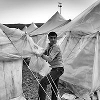 A Syrian refugee fixes a tent inside a refugee camp in Reyhanli, Turkey, Saturday, March 17, 2012. The number of Syrian refugees in Turkey is now about 17,000. March 2012.
