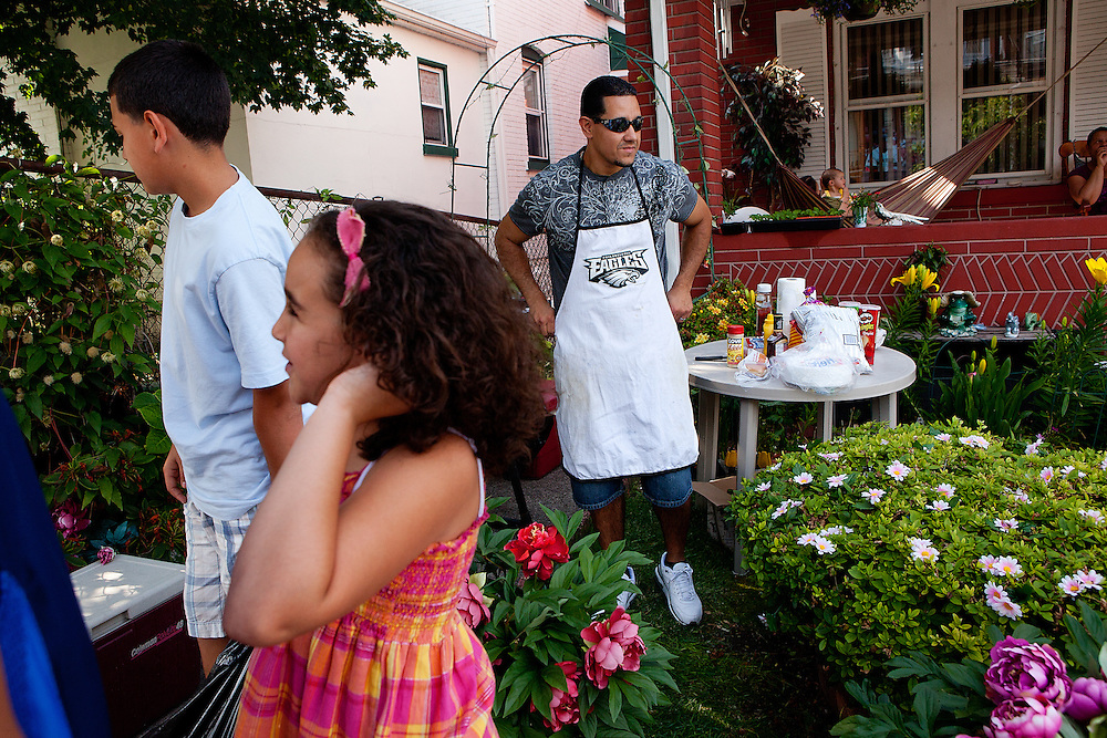 BETHLEHEM, PA – JUNE 19, 2011: Tony Figueroa, 37, dons a Philadelphia Eagles apron in preparation for a Father's Day barbecue in South Bethlehem with his children, Jayden and Kylie. Figueroa has family ties to Puerto Rico but grew up in the Lehigh Valley. He teaches English as a second language in Broughal Middle School in Bethlehem.<br />