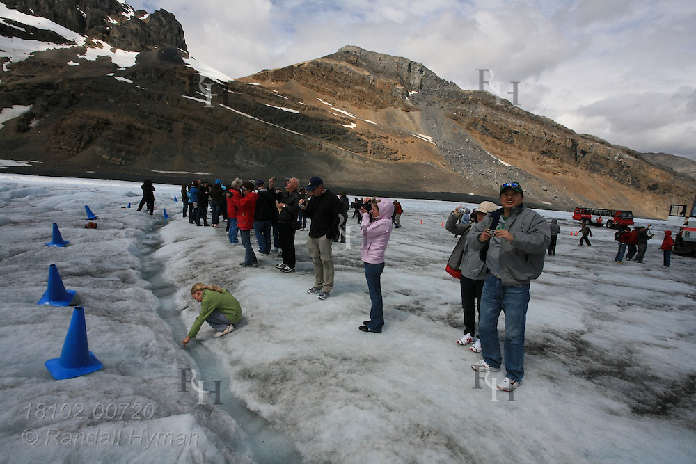 All-terrain tour bus passengers line up on Athabasca Glacier along perimeter cones to take pictures of the Columbia Icefield in Jasper National Park, Alberta, Canada.