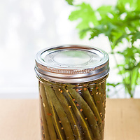Pickled green beans in a 500 ml wide-mouth Bernardin mason jar with decorative metal snap lid.