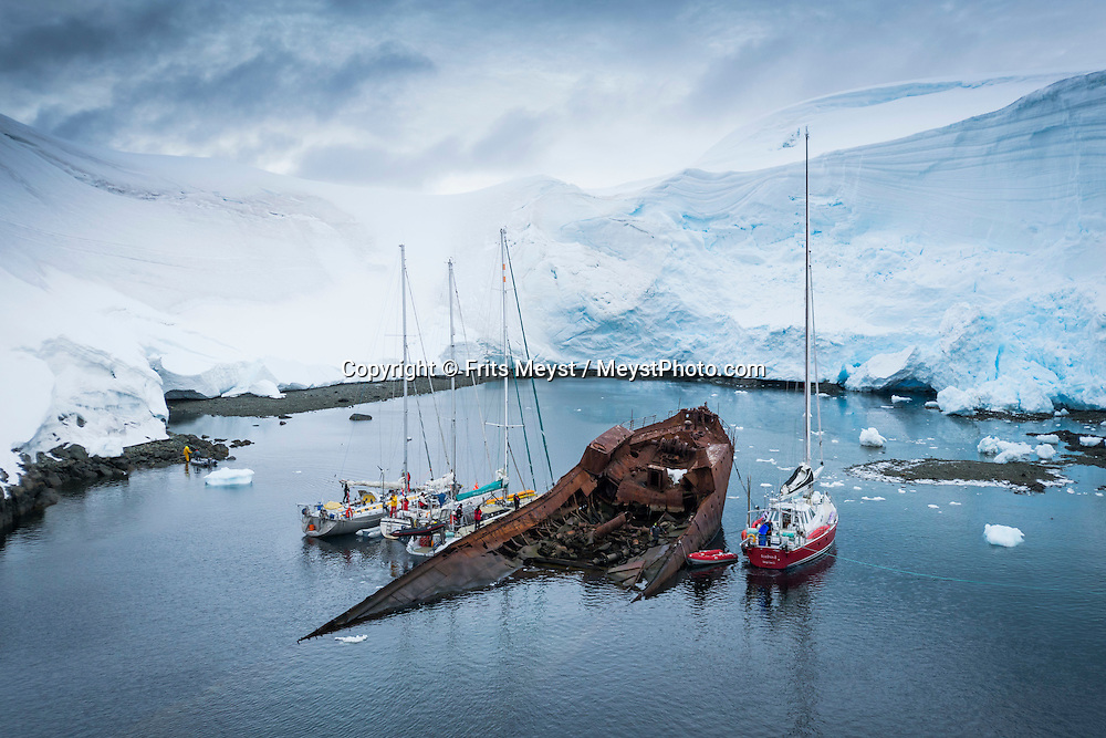 """Antarctica, February 2016. Gouvernøren was a factory ship operating in these waters until she burnt here in 1915 with a payload of 16,000 barrels of whale oil. She was intentionally wrecked as a consequence of the fire, the crew was picked up by other whaling vessels, part of the cargo was also saved, but the ship was lost, and lies there since then. Gouvernøren Harbour a small bay at Enterprise Island. This 1.5 miles long island lies at the NE end of Nansen Island in Wilhelmina Bay. The area was first charted as one feature and named """"Ile Nansen"""" by the Belgium Antarctic Expedition under Gerlache in 1898. Dutch Tallship, Bark Europa, explores Antarctica during a 25 day sailing expedition. Photo by Frits Meyst / MeystPhoto.com"""