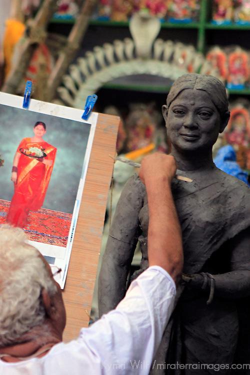 Asia, India, Calcutta. Clay artist sculpts from a photograph in the potter's village of Kumartuli in Calcutta.