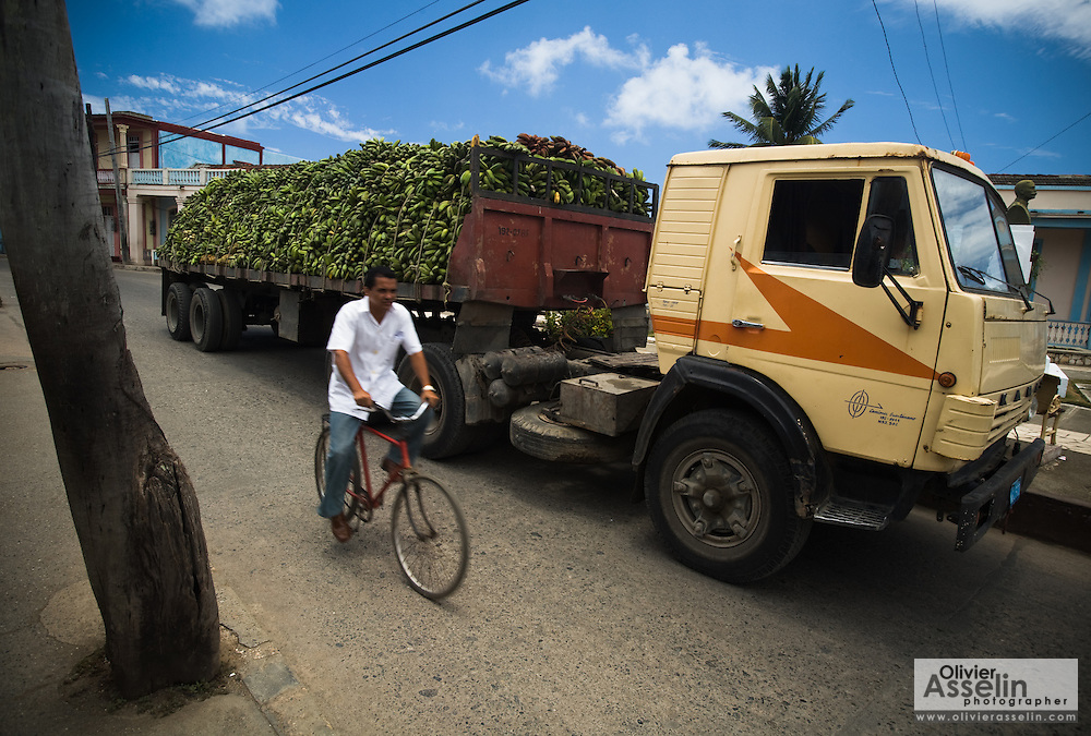 A man rides a bicycle past a truck carrying a load of bananas in Baracoa, Cuba on Friday July 11, 2008.