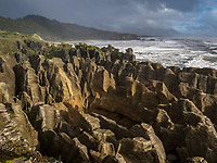 The Pancake Rocks are a heavily eroded limestone area where the sea bursts through several vertical blowholes during high tides. The 'pancake'-layering of the limestone is created by immense pressure on alternating hard and soft layers of marine creatures and plant sediments. South Island, New Zealand.