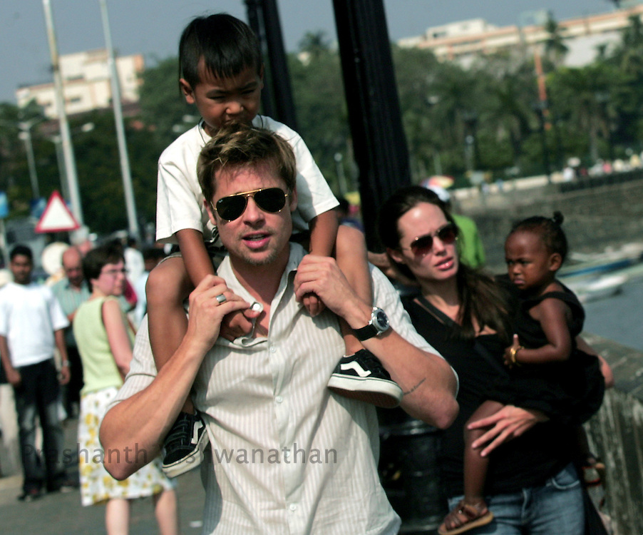 Hollywood star Brad Pitt (L) carries adopted son Maddox and Angelina Jolie (R) carries adopted daughter Zahara as they stroll outside their hotel in Mumbai November 12, 2006.