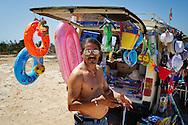 Lampedusa, Italia - 3 luglio 2011. Alì, tunisino, 55 anni, ritratto vicino al suo furgone pieno di articoli da mare. Alì possiede anche un 'attività commerciale su via Roma, la principale strada di Lampedusa. Mentre l'anno scorso riusciva a guadagnare 180 euro al giorno, quasta stagione esiva il suo guadagno è di media di 12 euro al giorno..Ph. Roberto Salomone Ag. Controluce