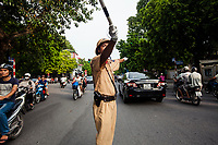 A policeman directs traffic at a major intersection in downtown Hanoi, Vietnam.