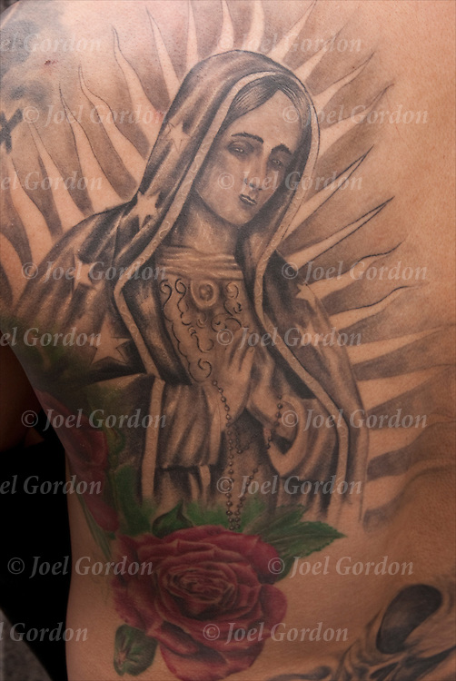 Close up of tattoo of Mexican Saint on his chest.<br /> <br /> Body art or tattoos has entered the mainstream it is known longer considered a weird kind of subculture.<br /> <br /> &quot;According to a 2006 Pew survey, 40% of Americans between the ages of 26 and 40 have been tattooed&quot;.