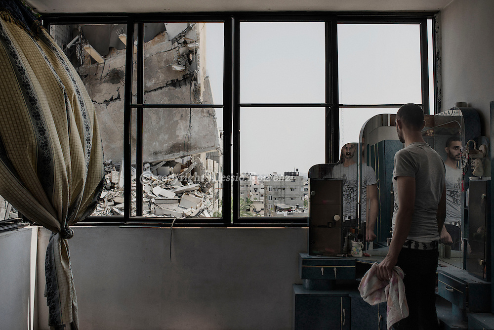 Gaza Strip, Gaza Street: A Palestinian man looks through the destroyed window of his house at the gutted by an overnight Israeli airstrike building in Omar Al Mukhtar street in Gaza City. The explosion killed 14 people of which 10 children. ALESSIO ROMENZI