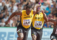 Athletics - 2017 IAAF London World Athletics Championships - Day Nine, Morning Session<br /> <br /> 4 x 100m Relay Men - Round 1<br /> <br /> Usain Bolt receives the baton from Michael Campbell (Jamaica) as he heads off down the home straight on the last leg at the London Stadium<br /> <br /> COLORSPORT/DANIEL BEARHAM
