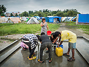 05 AUGUST 2015 - KATHMANDU, NEPAL:  People get water from a communal spigot in a large Internal Displaced Person (IDP) Camp in the center of Kathmandu. The camp is next to one the most expensive international hotels in Kathmandu. More than 7,100 people displaced by the Nepal earthquake in April live in 1,800 tents spread across the space of three football fields. There is no electricity in the camp. International NGOs provide water and dug latrines on the edge of the camp but the domestic waste water, from people doing laundry or dishes, runs between the tents. Most of the ground in the camp is muddy from the running water and frequent rain. Most of the camp's residents come from the mountains in northern Nepal, 8 - 12 hours from Kathmandu. The residents don't get rations or food assistance so every day many of them walk the streets of Kathmandu looking for day work.     PHOTO BY JACK KURTZ
