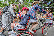 A family on a three man bike and tricycle in matching blazers - The Tweed Run, a very British public bicycle ride through London's streets, with a prerequisite that participants are dressed in their best tweed cycling attire. Now in it's 8th year the ride follows a circular route from Clerkenwell via the Albert Memorial, Buckinham Palace and Westminster.