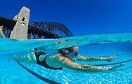 Underwater split level view of a swimmer in a North Sydney harbour bridge public swimming pool. Sydney. Australia.