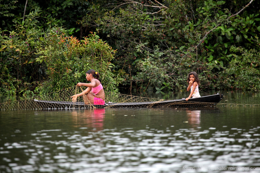 South America, Brazil, Amazon. A mother and daughter tend fishing nets by canoe on the Amazon.
