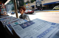 A passerby looks at various newspapers before buying one at a roadside stand in Caracas.  The Venezuelan media, both print and TV, is very biased.  Opposition media showed cartoons during the 2002 presidential coup in hopes of keeping the new government in power, and have done a shoddy job of reporting on any proof of opposition claims of fraud in the recent presidential referendum.